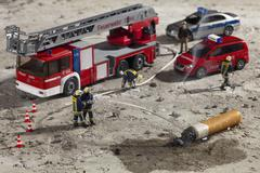 Miniature figurines of firemen using a hose to put out a smoking cigarette butt Stock Photos