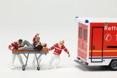 Miniature EMT hahmoja työntämisestä potilas paareilla jotta lelu ambulanssi Kuvituskuvat
