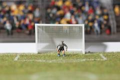 A miniature soccer goalie figurine guarding the goal post Stock Photos