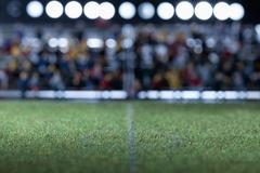 The center field of a miniature soccer field, spectator figurines in background - stock photo