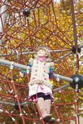 Girl standing on jungle gym Stock Photos
