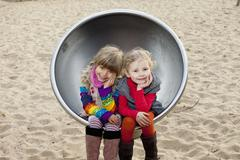 Two girls sitting on spherical metal chair in park Stock Photos