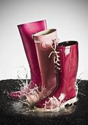 Three pink rubber boots splashing in a puddle Stock Photos