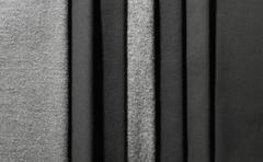 Varying shades of gray textiles hanging in a row - stock photo