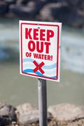 A Keep Out of Water sign posted on a rocky beach Stock Photos