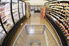 A shopping cart on an aisle in a supermarket, personal perspective - stock photo