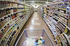 A shopping cart on an aisle in a supermarket, personal perspective Stock Photos