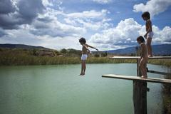 A boy jumping into water while his twin brother and friend watch Stock Photos