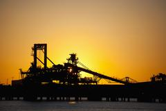 Silhouette of a bucket wheel reclaimer at an iron ore mine Stock Photos
