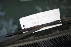 A handwritten note tucked behind a windshield wiper Stock Photos