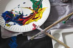 Heaps of acrylic paint on a paper plate and paintbrushes Stock Photos