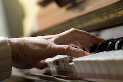 Piano chord pressed by woman's hand - stock photo