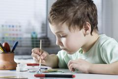 Boy Painting in workshop Stock Photos