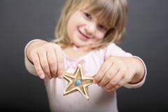 A girl holding out up a star shaped Christmas cookie Stock Photos