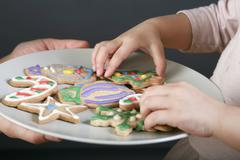 A mother sharing a plate of Christmas cookies with her daughter, focus on hands Stock Photos