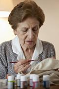 A senior woman painting on fabric Stock Photos