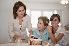 A woman serving cake for her mother and daughter Stock Photos