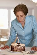 A senior woman blowing out a candle on a cake - stock photo