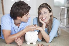 A young couple lying on the floor counting coins - stock photo