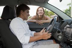 A woman leaning in car window smiling at boyfriend in the driver's seat Stock Photos