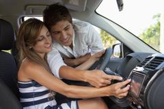 A man leaning in car window helping his girlfriend with the GPS Stock Photos