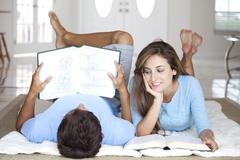 Stock Photo of A young couple lying on the floor studying with textbooks