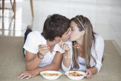A young couple kissing while eating breakfast - stock photo