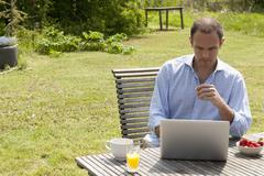 A man sitting at a table in his backyard having breakfast and using a laptop - stock photo