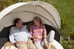 A couple reclining in a cabana in their backyard Stock Photos