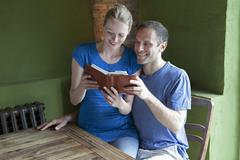 A couple reading a personal organizer together and smiling Stock Photos