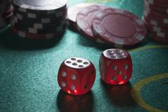 Two rolled sixes on a craps table, gambling chips in the background Stock Photos