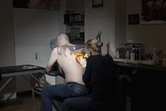 A female tattoo artist tattooing a man's back in a tattoo shop - stock photo