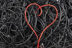 A red cord in a heart shape amongst tangled black cables and cords Stock Photos