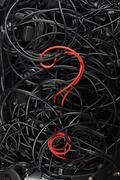 A single red cord in the form of a question mark amongst a tangle of black cords Stock Photos