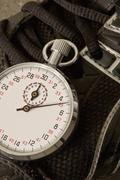 A stopwatch lying on top of a sports shoe, close-up Stock Photos