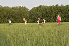 A woman standing in a field with four children Stock Photos