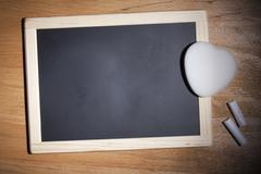 A small blank chalkboard with chalk and a heart shaped eraser Stock Photos