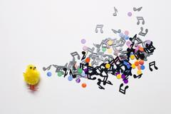 A toy Easter chick next to a group of musical notes and confetti Stock Photos