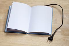 A hardcover book with an electric plug attached to it Stock Photos