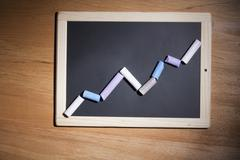 A line graph showing growth made with pieces of chalk and a chalkboard Stock Photos