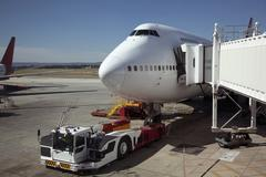 Jumbo jet attached to boarding bridge with tug in front Stock Photos