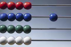 Neat rows of colored beads on an abacus with a single blue bead to the side Stock Photos