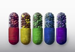 A row of vibrantly variously colored capsule pills, close-up Stock Photos