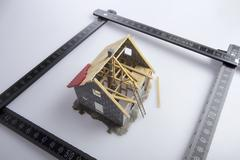 A partially constructed model of a house and a folding ruler Stock Photos