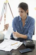 Woman at desk looking at receipts - stock photo