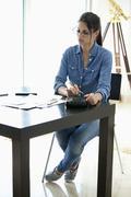 Woman using calculator at desk Stock Photos