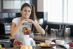 Woman leaning on blender full of fruit Stock Photos