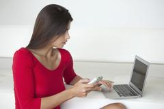 Woman in red using phone and laptop Stock Photos
