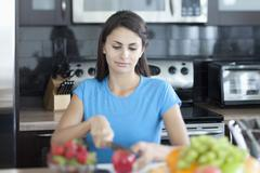 Woman slicing apple in kitchen - stock photo