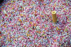 Cigarette stubbed out in multi colored pebbles Stock Photos